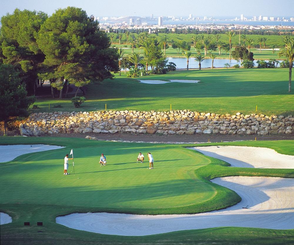 Golfeurs sur le green entouré de bunkers sur le parcours La Manga Club