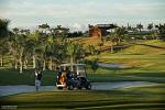 Vue sur le swing d'un golfeur et sa voiturette